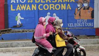"""Muslim women ride a motorbike past a coronavirus-themed mural in Jakarta, Indonesia, Thursday, Sept. 10, 2020. Writings on the mural read """"Let's fight coronavirus together"""""""