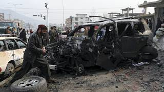 People gather near the site of a deadly bombing attack in Kabul, Afghanistan, Sunday, Dec. 20, 2020.