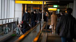 In this Friday Dec. 18, 2020, file photo, arriving and departing passengers use the flat escalators at Schiphol Airport, near Amsterdam, Netherlands.