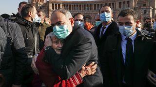 Армянский премьер Никол Пашинян обнимает плачущую женщину.