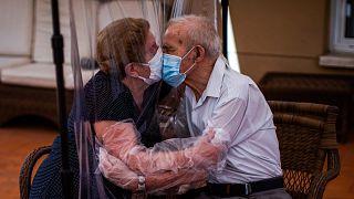 Agustina Cañamero e Pascual Pérez si baciano attraverso un telo di plastica per evitare il contagio da coronavirus in una residenza per anziani di Barcellona