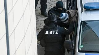 The defendant Stephan Balliet is escorted from the vehicle by court personnel upon his arrival at the district court in Magdeburg, Germany, Monday, Dec. 21, 2020.