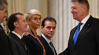 In this file photo taken on November 4, 2019 Romanian Minister of Finance Florin Citu (2nd L) shakes hands with Romanian President Klaus Iohannis (1st R) a