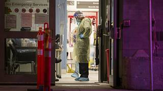 A Healthcare worker pauses during a lull in visitors at a COVID-19 testing center in Toronto, Sunday, Dec. 20, 2020.