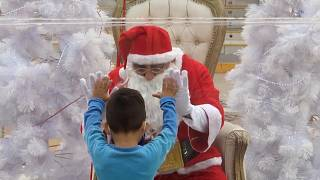 Boy placing hands up to Santa's hands on bubble
