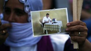 A supporter holds up a prison photograph of Selahattin Demirtaş in June 2020