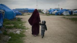 إمرأة تسير مع إبنها في مخيم الهول في شمال شرق سوريا