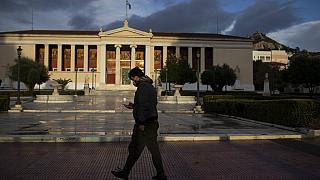 A man wearing a protective mask to curb the spread of the coronavirus walks in front of the Athens University building