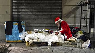 A homeless man, name given Rafael, wears a Santa Claus outfit as he prepares to have dinner by the side of a road, in Milan, Italy