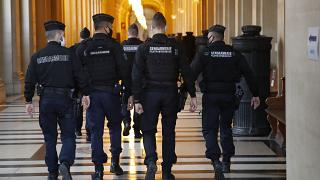FILE: French gendarmes walk in the corridor of the hall of justice, Thursday, Dec. 17, 2020 in Paris.