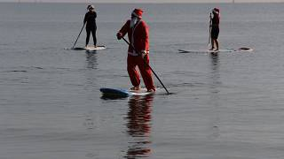 Members of a windsurfing center wear Santa Claus costumes as they paddle on stand up boards during Christmas celebrations in southern costal city of Larnaca, Cyprus