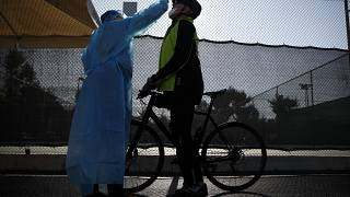 A medical staff member of the National Health Organization (EODY) conducts a COVID-19 rapid test on a bicycle rider at a drive-through testing site in Athens