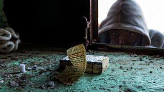 A boy who fled the conflict in Ethiopia's Tigray region looks at an Ethiopian priest's Bible near Umm Rakouba refugee camp in Qadarif, eastern Sudan.