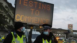 Police stand next to an electronic notice notifying about coronavirus testing to help clear a backlog of freight, truck and passengers outside the Port of Dover in Dover.