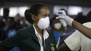 Nijerya'nın Lagos kentinde havaalanında ısı derecesi ölçülen bir kabin görevlisi