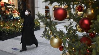A woman wears a face mask as she walks past a Christmas tree in New Bond Street, in London, Tuesday, Dec. 22, 2020.