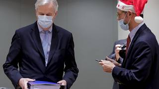 A collegue wears a Christmas hat as EU chief negotiator Michel Barnier, left, carries a binder of the Brexit trade deal during a special meeting in Brussels, Dec 25, 2020.