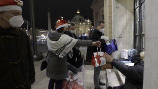 Voluntarios de la Comunidad de San Egidio distribuyen alimentos y regalos a las personas sin hogar fuera de la Plaza de San Pedro en el Vaticano, el 24 de diciembre de 2020.