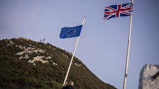 A worker lowers the EU flag at the British territory of Gibraltar, Friday Jan. 31, 2020.