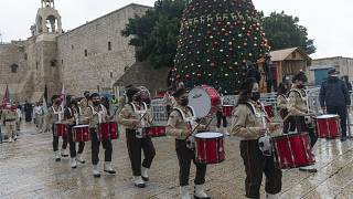 Palestinian scout bands parade through Manger Square at the Church of the Nativity, in the West Bank city of Bethlehem, Thursday, Dec. 24, 2020.