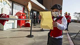 طفل يقرأ رسالة الأمنيات إلى سانتا كلوس قبل أن يضعها في صندوق البريد