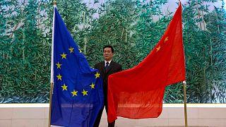 مقام چینی در کنار پرچم کشورش و اتحادیه اروپا در جریان مذاکرات سال ۲۰۱۳