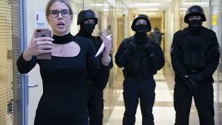 FILE - Russian opposition activist Lyubov Sobol reports live by phone as policemen stand guard at the Foundation for Fighting Corruption office in Moscow, Russia.