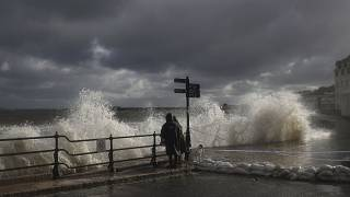 FILE PHOTO - People watch as waves crash along the coast at Swanage in Dorset, England, Friday, Oct. 2, 2020.