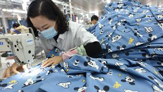 A woman wearing a mask labors in a garment factory in Donghai county in east China's Jiangsu province Tuesday, Oct. 27, 2020.