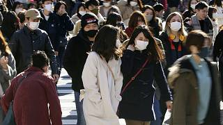 People wearing face masks to help curb the spread of the coronavirus walk around the scrambled intersection at the Shibuya shopping district in Tokyo Saturday, Dec. 26, 2020.