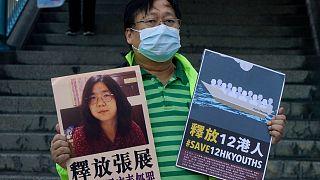 یک کنشگر تایوانی تصویری از ژانگ ژان را در دست دارد