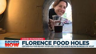 A woman picks up a glass of wine through a 'buchetta' (little hole) in Florence