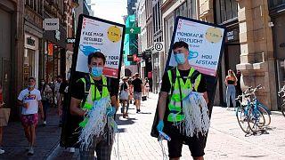 شابّان هولنديان في أمستردام يوزعان أقنعة واقية يحملان يافطات تحث على التباعد الإجتماعي للحيولة دون العدوى بفيروس كورونا