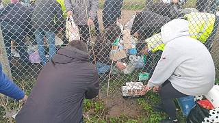 Local volunteers tried to get food to the drivers by pushing it under the fence