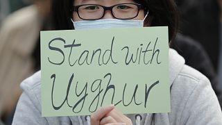 Hong Kong'da düzenlenen gösteriler sırasında Uygurlarla dayanışma içerisinde olduğunu belirten bir döviz taşıyan eylemci