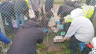 Volontari locali fanno passare le provviste sotto la recinzione per aiutare gli autisti