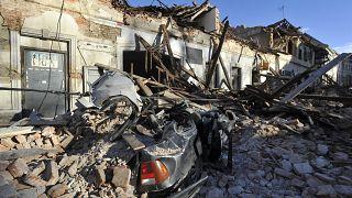 بقايا سيارة مغطاة بالحطام والمباني التي تضررت في الزلزال