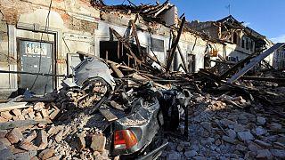 Resti di un'auto coperta da detriti e di edifici danneggiati dal terremoto a Petrinja, Croazia