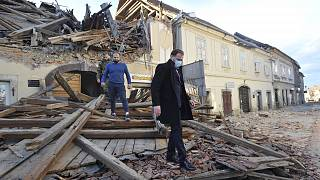 People move through remains of a building damaged in an earthquake, in Petrinja, Croatia, Tuesday, Dec. 29, 2020.