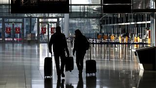 People walk through a deserted check-in hall at the airport in Munich, Germany, Saturday, December 26, 2020.