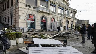 أناس ينظرون إلى شرفات المطاعم المتضررة جراء العاصفة على رصيف نابولي. 2020/12/29