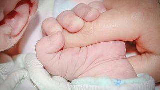Baby umklammert Finger eines Erwachsenen
