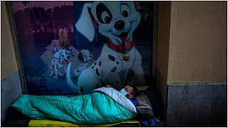 متشرد ينام في الشارع مرتديا قناعا في برشلونة- إسبانيا