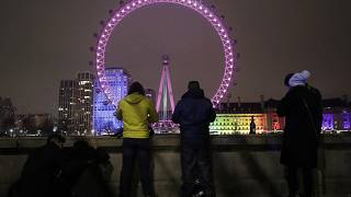 A small group of people look across from the embankment towards the London Eye ferris wheel by the River Thames in London as the New Year starts in London, Friday, Jan 1, 2021