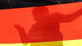 Egy szélsőjobbos nagygyűlés részvevője a német zászló árnyékában