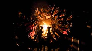 Migrants stretch their hands above a fire at the Lipa camp outside Bihac, Bosnia, Wednesday, Dec. 30, 2020, after hundreds failed to be relocated from the burnt-out tent camp.