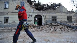 A rescuer walks past a building damaged in Petrinja.