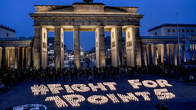 Activists light candles in front of the Brandenburg Gate during a protest marking the fifth anniversary of the Paris Agreement signing.