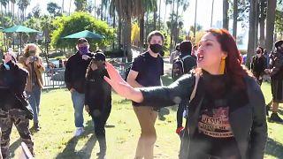 Una mujer grita 'Jesús' e interpone su mano cuando una persona le pide que se ponga la mascarilla en Los Ángeles, California