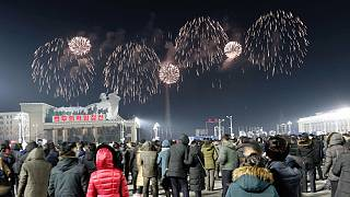 A fireworks display decorates the night sky to celebrate the New Year, as crowds of people look on, at Kim Il Sung Square in Pyongyang, early Friday, Jan., 1, 2021